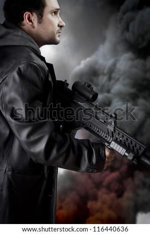 Man with long leather jacket and assault rifle, black smoke background - stock photo