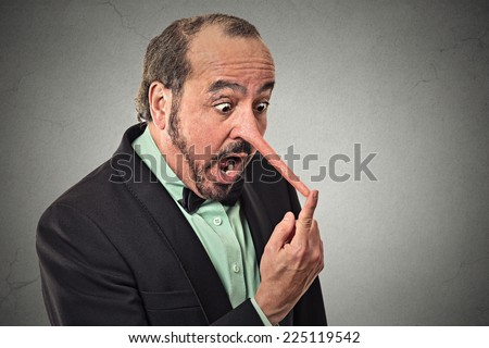 Man with long nose isolated on grey wall background. Liar concept. Human face expressions, emotions, feelings. - stock photo