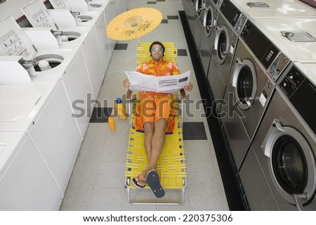 Man with lounge chair and umbrella reading newspaper in laundromat - stock photo