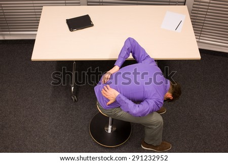 man with lower back pain in office work exercising - stock photo