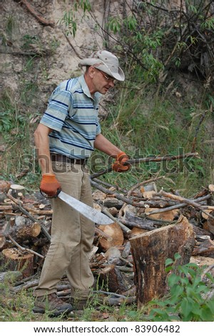 Man with machete chop logs for firewood.Ukraine - stock photo