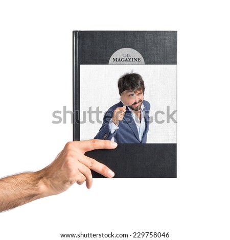 Man with magnifying glass printed on book - stock photo
