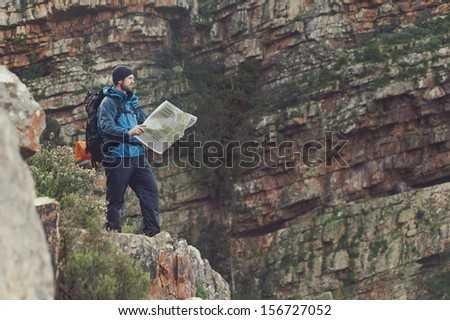 Man with map exploring wilderness on trekking adventure - stock photo