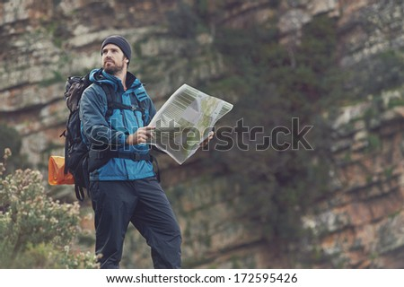Man with map exploring wilderness on trekking adventure - stock photo
