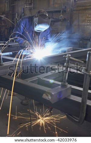 man with mask welding at steel construction at workshop