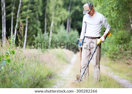 Man with metal detector and shovel searching for coins on old road