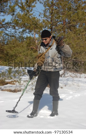 Man with metal detector in the forest at  early spring. Near Kiev,Ukraine - stock photo