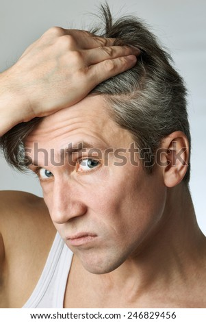 Man with mirror looking at his hair on gray background - stock photo