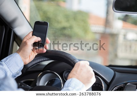 Man with mobile distracted and driving your car - stock photo