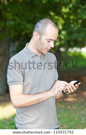 Man with Mobile Phone at Park - stock photo