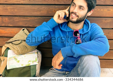 Man with mobile phone - Attractive young guy talking by telephone -Trendy cheerful  hipster  - Handsome smiling student sitting outdoors - Modern concept of travel and web technology - Modified map    - stock photo