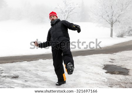 Man with mobile phone is slipping on a freezy way - stock photo