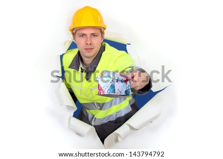 Man with money balancing on trowel - stock photo