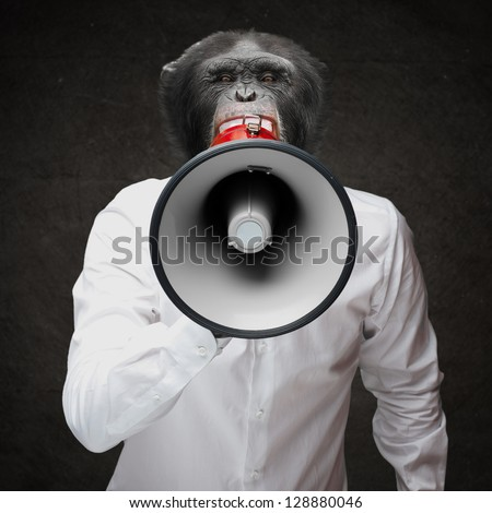 Man With Monkey Head Shouting Through Megaphone On Black Background - stock photo