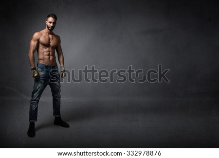 man with muscles waiting for fight, dark background - stock photo