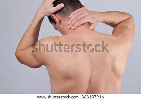 Man with neck and back pain. Man rubbing his painful back close up. Pain relief,  chiropractic concept - stock photo