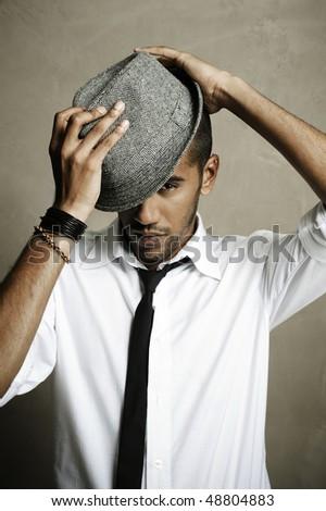 Man with necktie poses in studio with fedora - stock photo