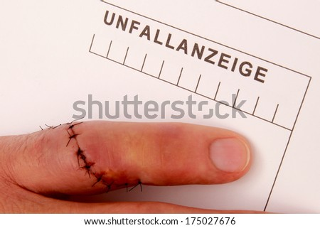 Man with needled finger fills out a accident report - stock photo