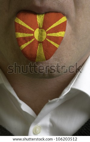 man with open mouth spreading tongue colored in macedonia flag as symbol of values like teaching, learning, multilingual speaking of different languages - stock photo