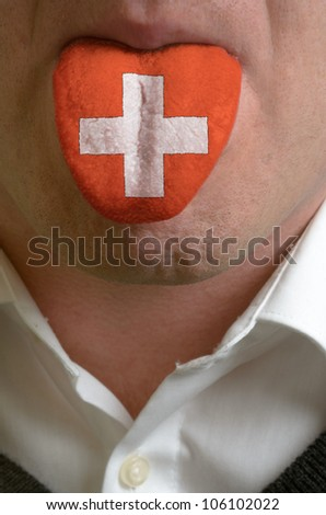 man with open mouth spreading tongue colored in switzerland flag as symbol of values like teaching, learning, multilingual speaking of different languages - stock photo
