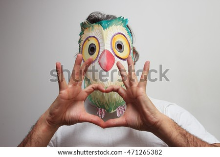 man with owl mask doing love gesture