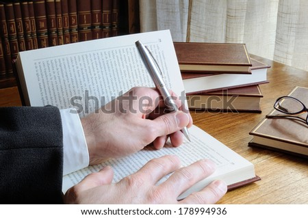 man with pen in hand looking for references in a book - stock photo