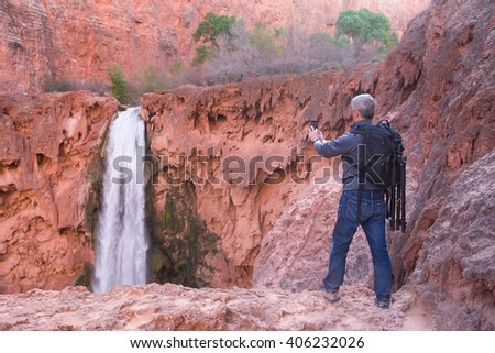 Man with photo gear takes picture of Mooney Falls with his mobile phone, Havasu Canyon, Arizona, USA - stock photo