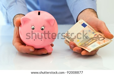Man with piggybank and stack of euro banknotes.