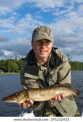 Man with pike trophy - stock photo
