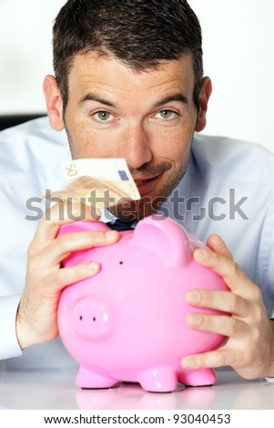 man with pink piggy bank and fifty euro banknote - stock photo