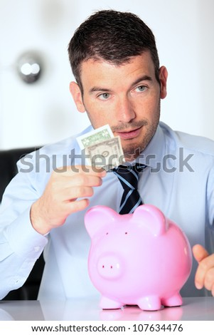 man with pink piggy bank and one dollar bill - stock photo
