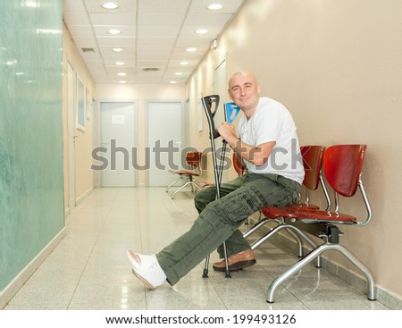 man with  plaster on his leg sits in  hospital corridor