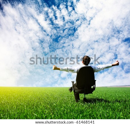Man with raised hands sitting on chair on green meadow - stock photo