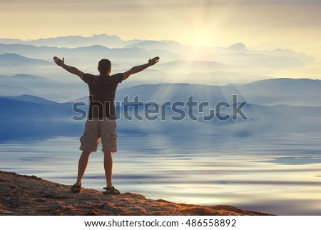 Man with raised hands standing on a shore of the mountain lake and enjoy sunrise