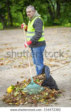 Man with rake collects leaves - stock photo