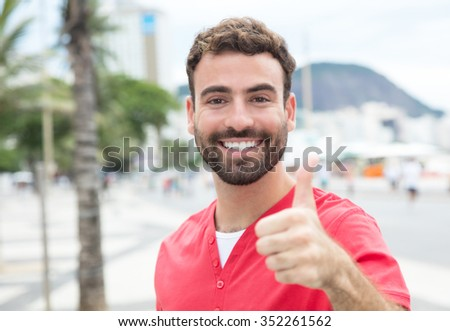 Man with red shirt and beard in the city showing thumb - stock photo