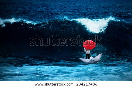 Man with red umbrella standing in a paper boat in rough sea - crisis concept - stock photo