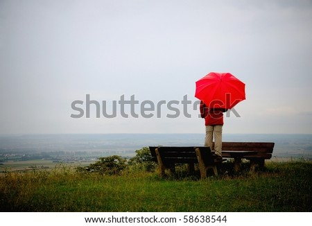 Man with red umbrella standing on a viewpoint at a rainy day in autumn