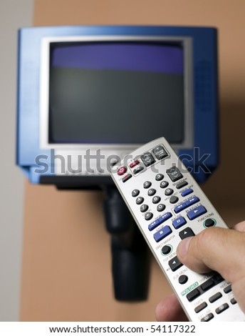 Man with remote is watching television program