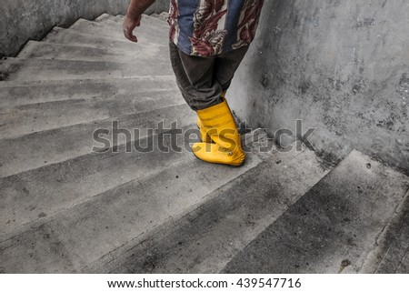 Man with safety boot walking down the stairs