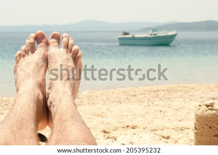 Man with sandy feet relaxing on a beach. Close-up with foot. - stock photo