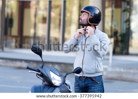 man with scooter takes off helmet  - stock photo