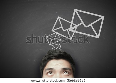 Man with sending message concept on the blackboard background. - stock photo