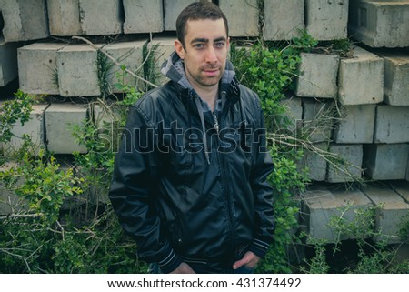 Man with serious face posing outdoor in abandoned industrial place. - stock photo