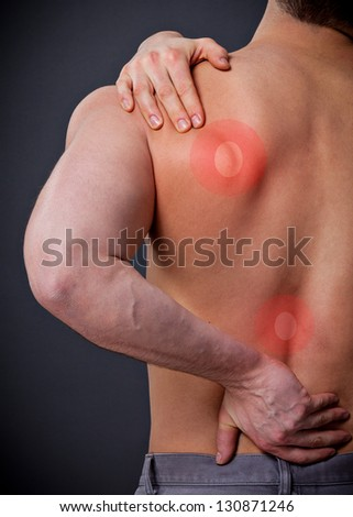 Man with severe back pain holds the shoulder - stock photo