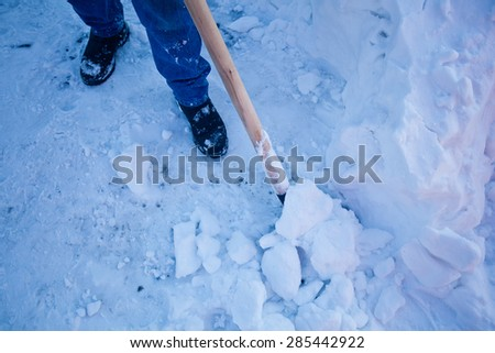 Man with shovel removing snow near his house during a snowy winter day - stock photo