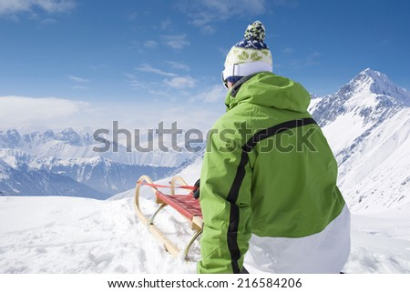 Man with sled on mountain top - stock photo