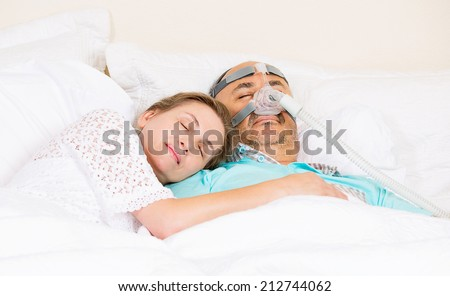Man with sleeping apnea and CPAP machine, devise, asleep peacefully with wife in bedroom their house. Healthcare management patient with sleep apnea. Human respiratory, airway, system health issues. - stock photo