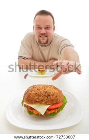 Man with small hamburger reaching for a bigger one - diet choices concept - stock photo