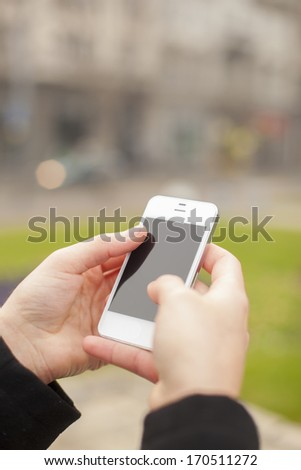 Man with smart phone in hand, urban street, blurred background - stock photo